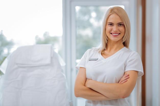 Cosmetologista experiente e encantada sorrindo para você enquanto o convida em suas clínicas