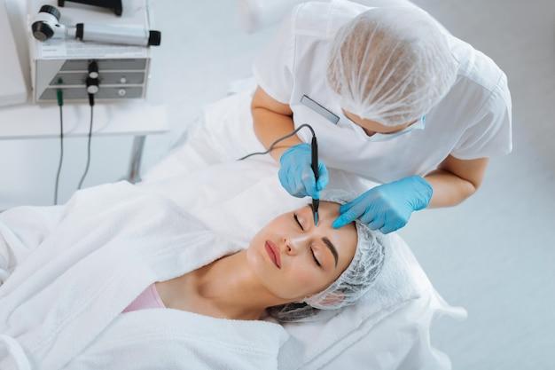 = cosmetologista experiente e inteligente removendo uma verruga enquanto trabalhava na clínica