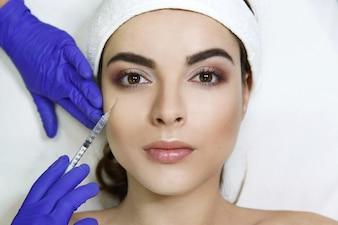 Cosmetologista faz injeção de beleza no rosto da mulher na clínica