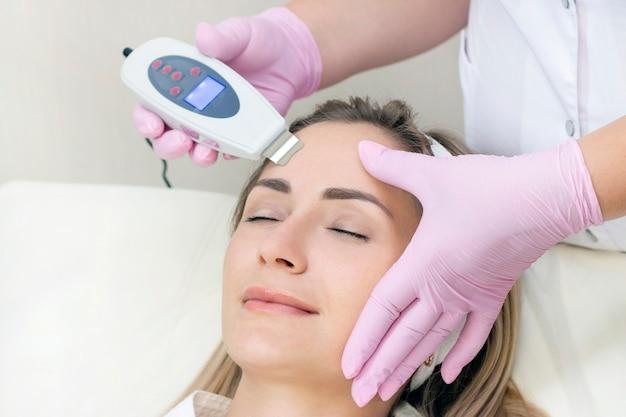 Cosmetologista faz limpeza ultrassônica do rosto de uma jovem.