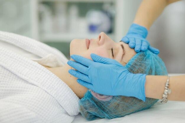 Cosmetologista faz massagem facial em salão de beleza