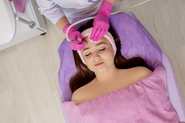 Cosmetologista faz o procedimento microdermoabrasão da pele facial de uma mulher jovem e bonita em um salão de beleza.