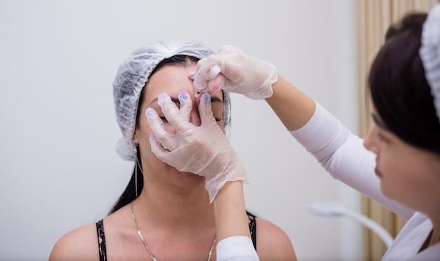 Cosmetologista faz uma injeção de beleza para uma cliente no sofá