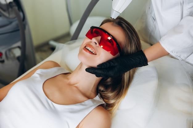 Cosmetologista fazendo depilação a laser em seu cliente.