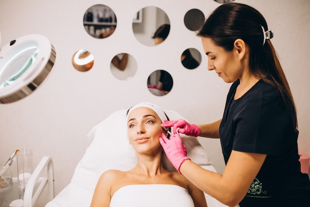 Cosmetologista fazendo injeções no rosto de uma mulher em um salão de beleza