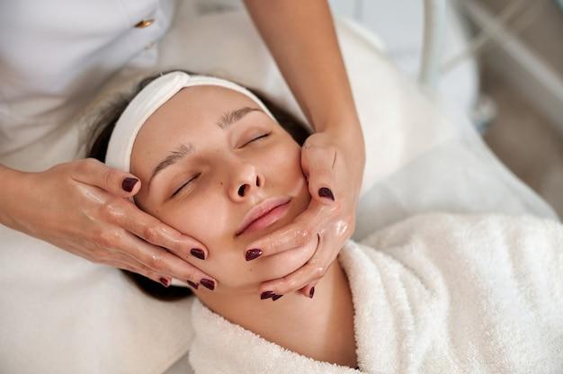 Cosmetologista fazendo lifting facial de massagem para rosto e pescoço de mulher. fechar-se
