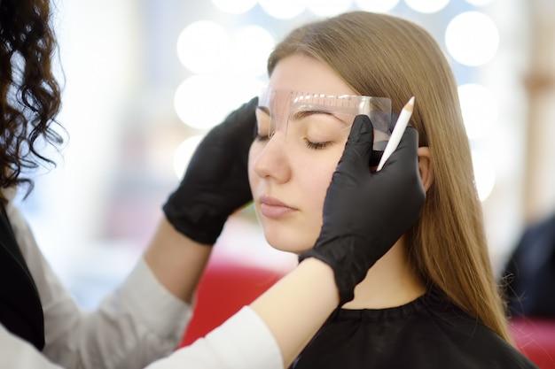 Cosmetologista fazendo maquiagem de sobrancelhas