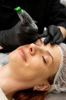 Cosmetologista fazendo maquiagem definitiva para sobrancelhas