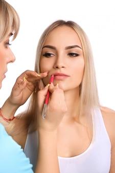 Cosmetologista fazendo maquiagem permanente nos lábios da mulher