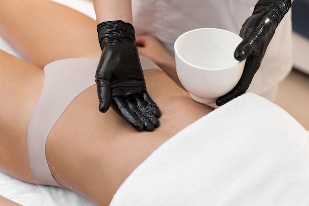 Cosmetologista fazendo massagem anticelulite e descamação do abdômen com sal