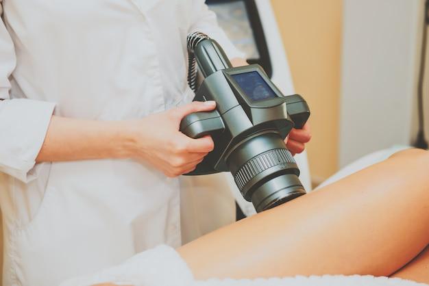 Cosmetologista fazendo massagem com aparelho nas pernas do cliente feminino, close-up.