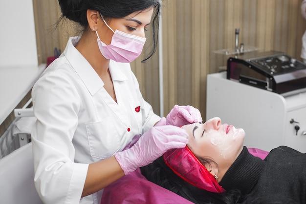 Cosmetologista fazendo massagem facial no paciente e máscara facial. procedimento anti-envelhecimento e alisamento em salão de beleza.