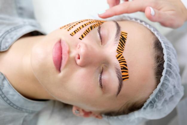 Cosmetologista fazendo o procedimento de gravação de rosto usando fitas coloridas de tigre no salão de beleza