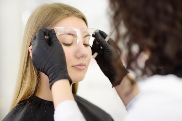 Cosmetologista fazendo sobrancelhas maquiagem.