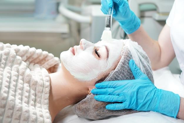 Cosmetologista fazendo tratamento cosmético com máscara facial para a jovem