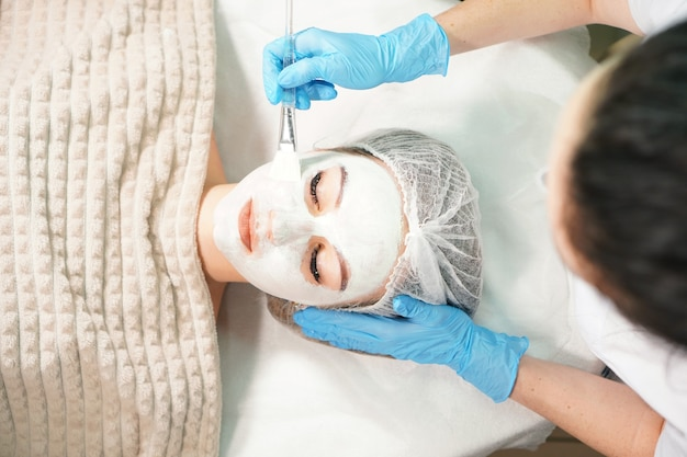 Cosmetologista fazendo tratamento cosmético com máscara facial para a mulher bonita.