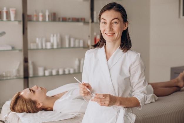 Cosmetologista fazendo tratamento facial e aplicando máscara facial