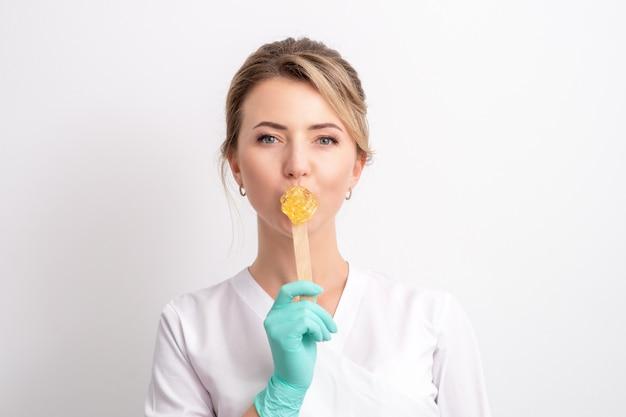 Cosmetologista feminina segurando a vara com cera.
