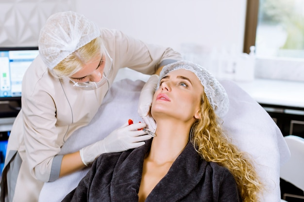 Cosmetologista jovem médico feminino fazendo injeção no rosto e pescoço de jovem loira. menina recebe injeções faciais de beleza no salão.