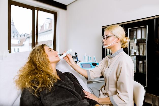 Cosmetologista jovem usa ferramenta especial para diagnóstico detalhado da condição da pele, presença de doenças de pele. linda mulher deitada no sofá.