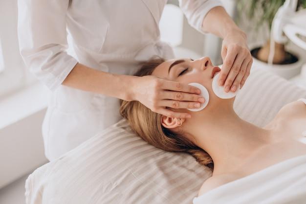 Cosmetologista limpando rosto com almofadas de algodão