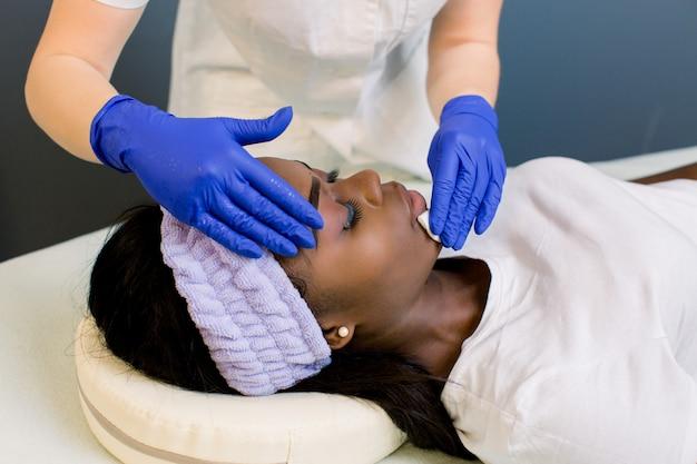 Cosmetologista, limpeza de rosto de uma jovem mulher africana com um algodão. remoção de cosméticos com discos higiênicos.