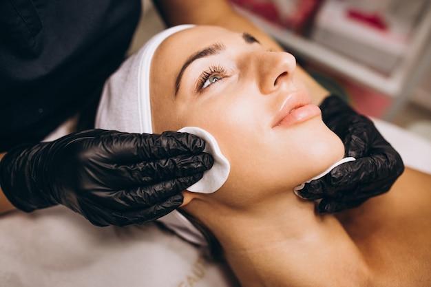 Cosmetologista, limpeza de rosto de uma mulher em um salão de beleza