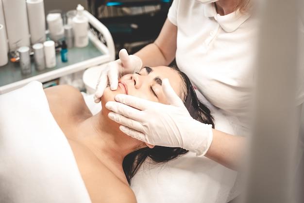 Cosmetologista mancha o rosto do paciente com creme nutritivo. massagem facial