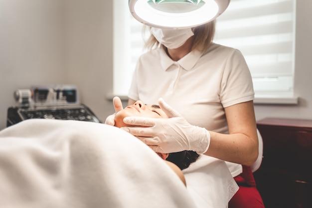 Cosmetologista massageia o rosto do cliente