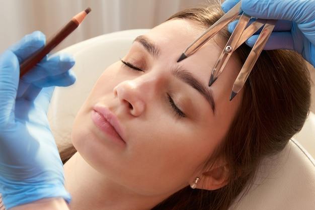 Cosmetologista mede as proporções das sobrancelhas com a régua.
