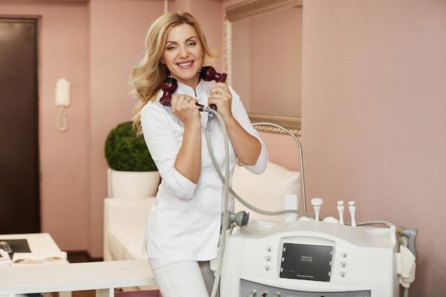 Cosmetologista médica em uniforme médico, sorrindo e mostrando o dispositivo para o procedimento de lifting facial não cirúrgico