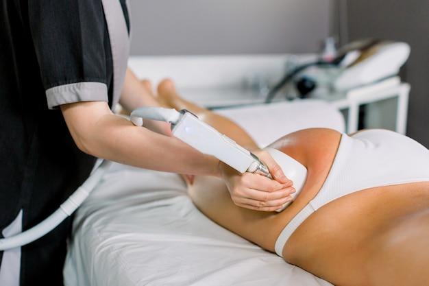 Cosmetologista médica fazendo massagem com rolo com aparelho nas coxas do cliente feminino, close-up. massagem com rolos no centro de spa médico