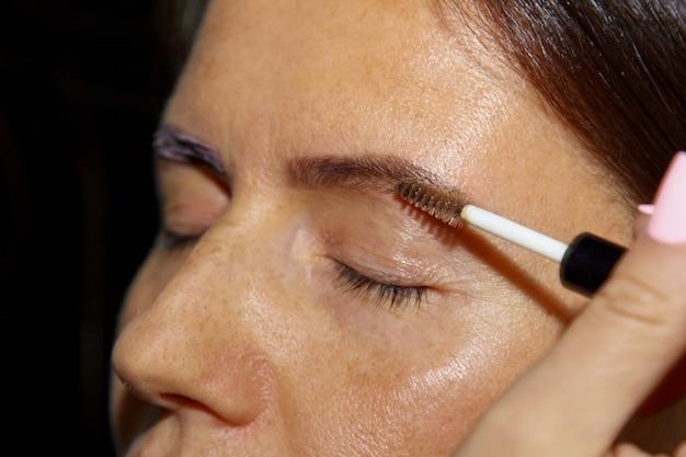 Cosmetologista - o maquiador pinta o henna nas sobrancelhas previamente arrancadas, desenhadas e aparadas em um salão de beleza em uma sessão de correção. facial profissional.