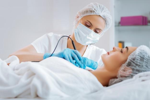 Cosmetologista profissional inteligente usando um dispositivo moderno para remover imperfeições da pele