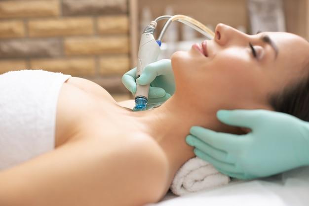Cosmetologista profissional realizando procedimento de dermoabrasão na pele de jovem cliente satisfeito