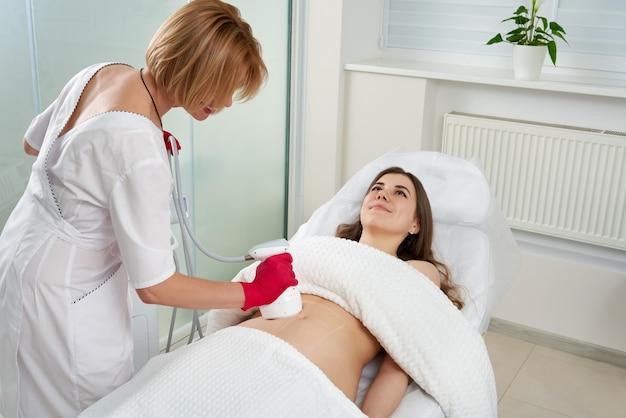 Cosmetologista profissional realizando procedimento de levantamento por radiofrequência no estômago de uma mulher