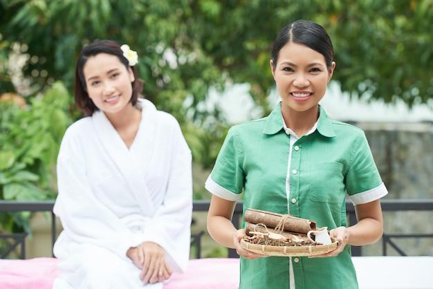 Cosmetologista profissional segurando a bandeja com ervas para procedimento de spa
