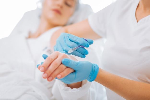 Cosmetologista profissional simpática segurando a mão do cliente enquanto aplica uma injeção lá