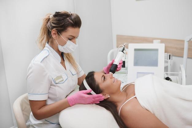 Cosmetologista profissional trabalhando em clínica de beleza, dando tratamento facial a uma cliente