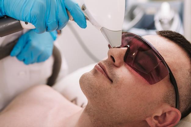 Cosmetologista profissional usando dispositivo de depilação a laser em seu cliente masculino