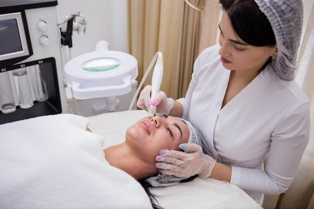 Cosmetologista realiza um procedimento facial para um cliente em um sofá