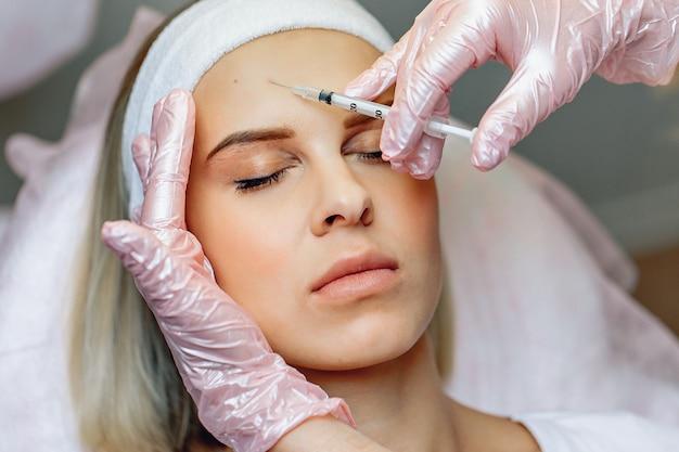 Cosmetologista realizando injeções de botox para rejuvenescer a parte frontal do rosto.