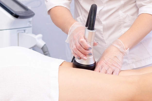Cosmetologista, reduzindo a celulite nos quadris de uma paciente do sexo feminino, usando aparelho de cavitação por ultrassom.