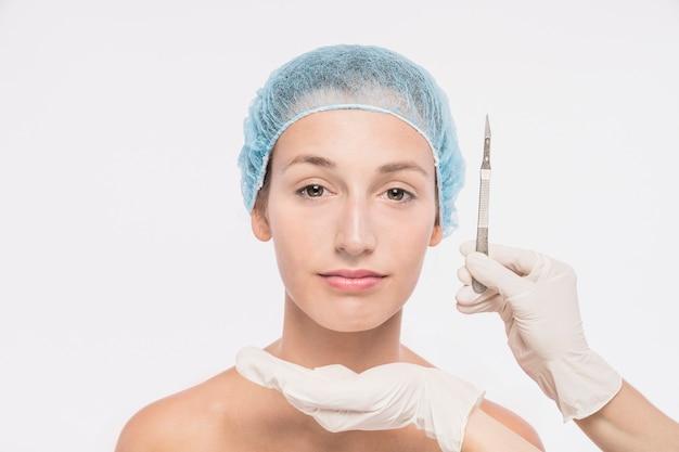Cosmetologista segurando bisturi perto do rosto de mulher