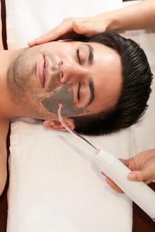 Cosmetologista usando dispositivo especial ao fazer limpeza ultrassônica durante procedimento de spa em salão de beleza, vista de cima
