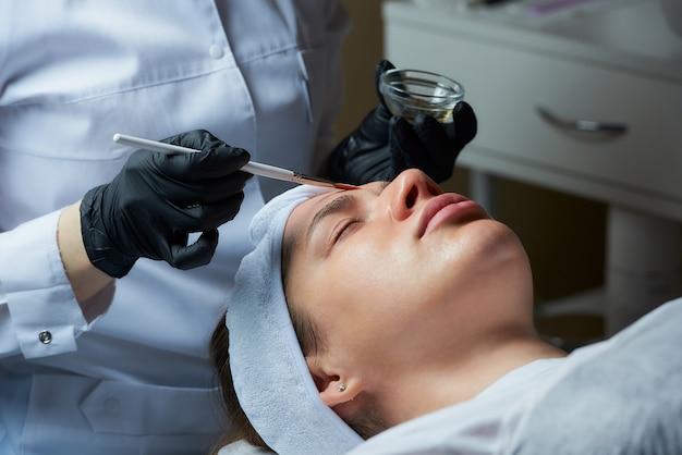 Cosmetologista usando luvas médicas descartáveis usa um pincel para aplicar um peeling superficial transparente
