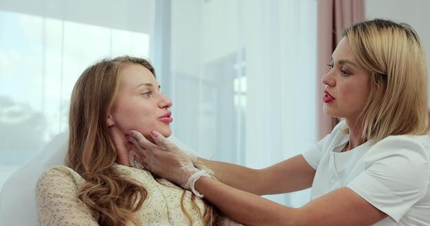 Cosmetologistas tocando e examinando a pele facial de uma mulher. rosto de mulher sendo verificado por esteticistas.
