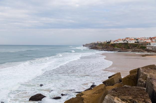 Costa atlântica com surfa em dia nublado
