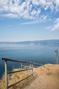 Costa com cercas metálicas cercada pelo mar com montanhas ao fundo