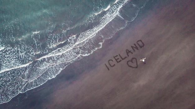 Costa da praia da islândia com ondas, menina e imagem de um coração